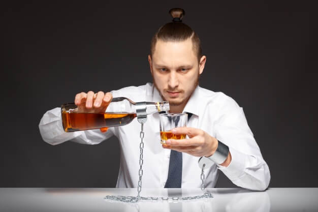 Alcohol addict pouring whiskey